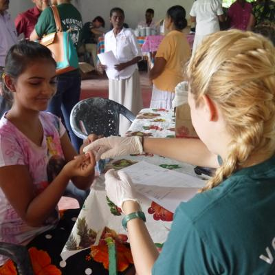 Transition Year volunteer measures the blood sugar of a young girl in Sri Lanka.